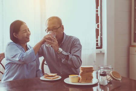 Retirement senior lifestyle living concept, Asian elderly couple drinking milk for breakfast together