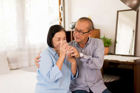 Asian elderly couple drinking milk for breakfast in bedroom together, Retirement senior lifestyle living concept