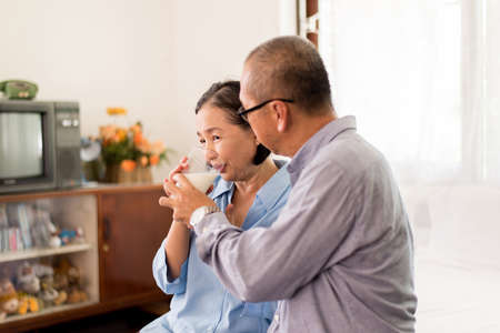 Asian elderly couple drinking milk for breakfast at home, Retirement senior lifestyle living concept