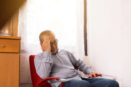 Senior Asian elderly man having migraine and headache pain while sitting on sofa at home, Elderly healthy concept
