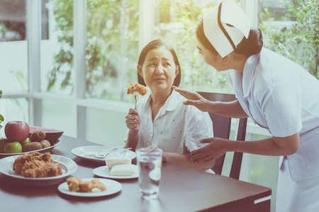 Krankenschwesterhände stoppen für eine ältere asiatische Frau, die sich mit einer Mahlzeit glücklich fühlt, ein gesundes Konzept für ältere Menschen Standard-Bild
