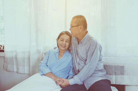 Couple Asian senior encourage and hugging on bed together,Happy and smiling,Positive thinking