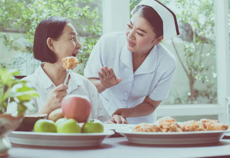 Nurse hands stop to senior Asian woman feeling happy with meal,Elderly healthy concept