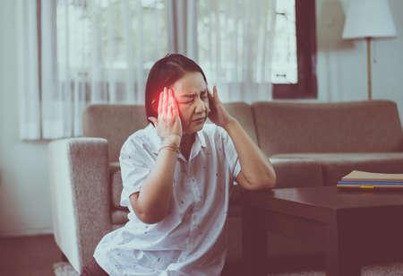 Rijpe Aziatische vrouwen met migraine en hoofdpijn thuis, Senior gezond concept
