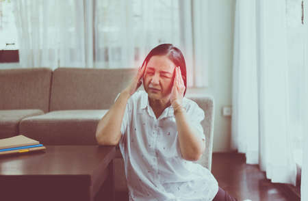 Mature Asian woman having migraine and headache pain at house,Senior healthy concept