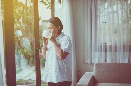 Mature Asian woman drinking hot coffee near window in the morning at home,Happy and smiling,Positive thinking
