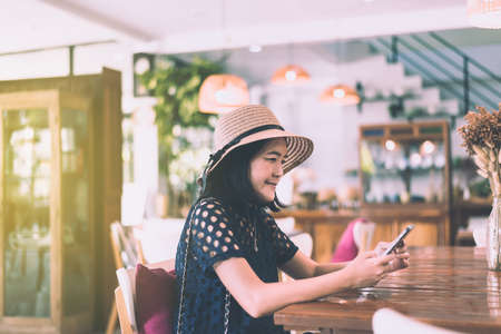 Beautiful Asian woman using mobile phone and sitting in cafe,Happy and smiling,Positive thinking