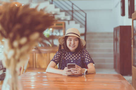 Beautiful Asian woman using mobile phone and sitting in coffee shop,Happy and smiling,Free time