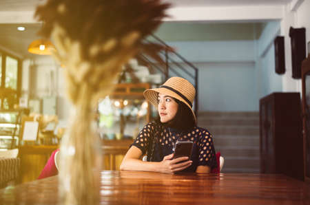 Beautiful Asian woman sitting and looking something in coffee shop,Happy and smiling,Free time