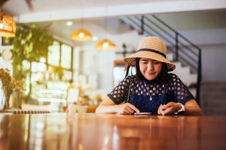 Beautiful Asian woman using smart phone and sitting in cafe,Happy and smiling,Positive thinking