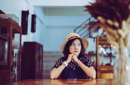 Beautiful Asian woman sitting and looking something in cafe,Positive thinking Imagens