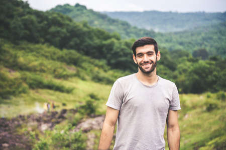 Portrait of young handsome man with beard standing at outdoor,Happy and smiling,Travelling concept