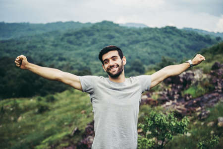 Portrait of young handsome man happy and smiling,Travel at outdoor,Hand raise up