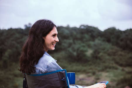Portrait of young beautiful woman happy and smiling while sitting at outdoor,Travel concept
