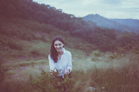 Portrait of young beautiful woman happy and smiling while looking flower,Travel at outdoor