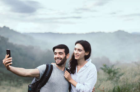 Woman and man taking a phone selfie together outdoor,Couple in love,Happy and smiling