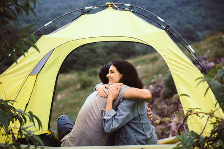 Couple lover hugging together sitting in tent feeling happy and smiling,Enjoying camping
