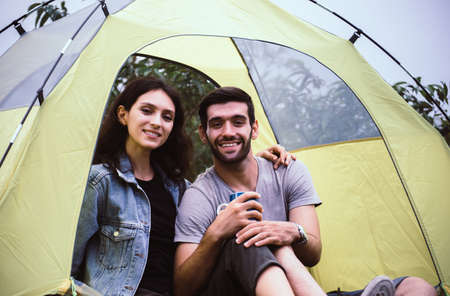 Couple lover looking camera while sitting inside tent together feeling happy and smiling,Enjoying camping