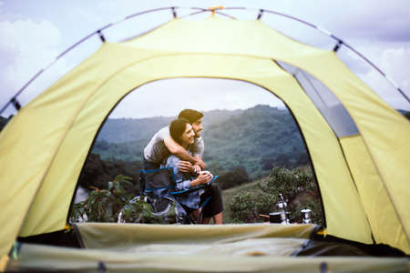Couple lover hugging together outside tent feeling happy and smiling,Enjoying camping
