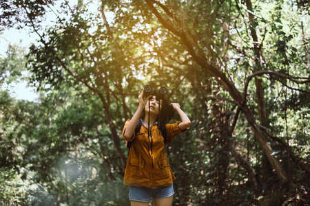 Portrait of travel young asian woman using binoculars in forest,Enjoying with bird watching