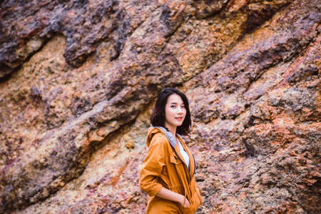 Portrait of traveler asian woman standing near cliff and looking camera at outdoor,Happy and smiling