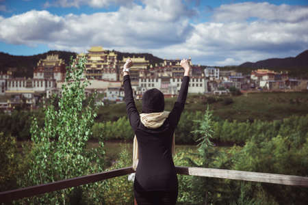Happy and cheering woman stands with raised up hands and looking beautiful view in the morning