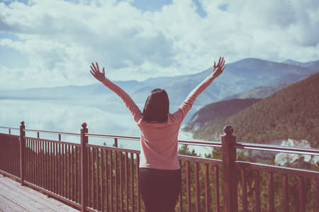 Happy and cheering woman stands with raised hands and looking beautiful amazing view at lake in the morning