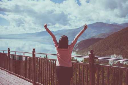 Happy and cheering woman stands with raised hands and looking beautiful while looking amazing view at lake in the morning