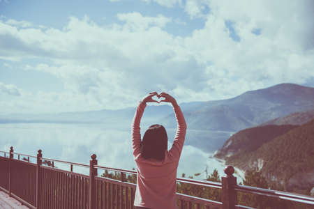 Happy and cheering woman stands with showing hands heart shape and looking beautiful while looking amazing mountains view at outdoor