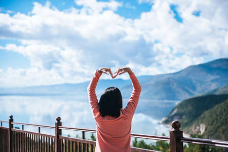 Happy woman stands with showing hands heart shape and looking beautiful while looking amazing mountain view at outdoor