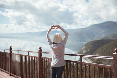 Happy and cheering woman stands with showing hands heart shape and looking beautiful while looking amazing mountains view at outdoor,Back view