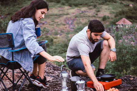 Couple lover cooking food for dinner outside tent together,Enjoying camping concept
