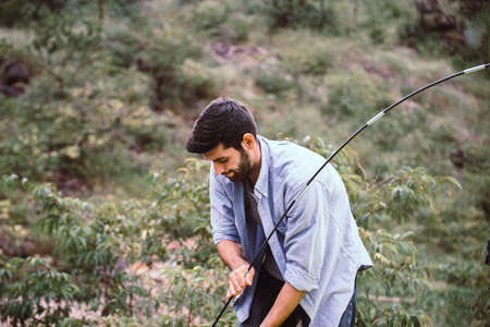 Traveller man putting up a tent in nature,Enjoying camping concept Imagens