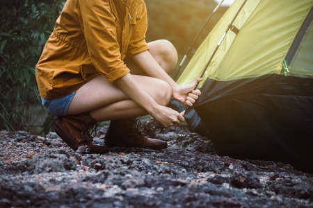 Traveller woman putting up a tent in nature,Enjoying camping concept