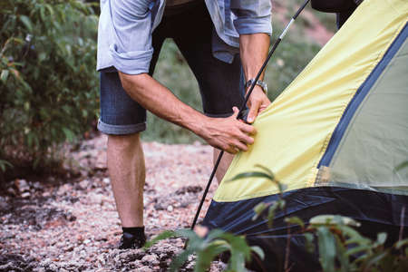 Traveller male putting up a tent in nature,Enjoying camping concept Imagens