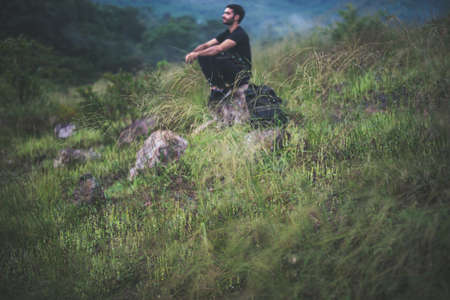 Blured of traveller male with backpack sitting on rock at nature,Meditations to calm your mind and body