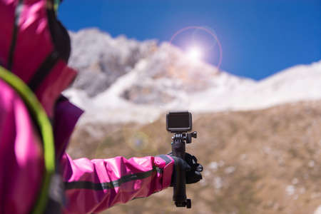 Hand traveler woman holding action camera at snow mountain,Navigation for travel,Close up Foto de archivo - 133743825