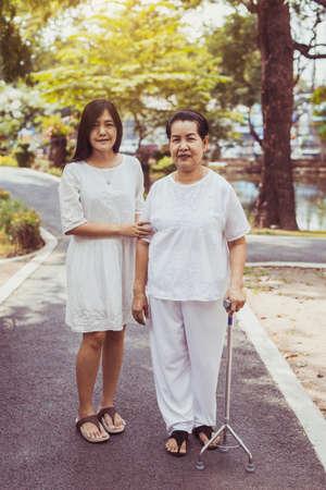 Anciana mujer asiática caminando para hacer ejercicio físico con bastón en el parque, cuidado y apoyo de la hija, concepto de Asia social de ancianos Foto de archivo