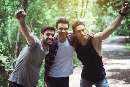 Happy man traveler friends hugging with hands raise up together at nature,Enjoying backpacking concept Foto de archivo - 133744034