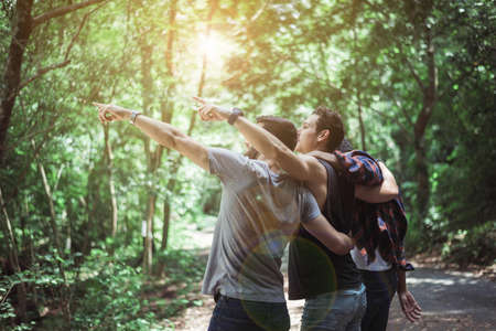 Happy traveler friends hugging and pointing something together at nature,Enjoying backpacking concept Foto de archivo - 133744031