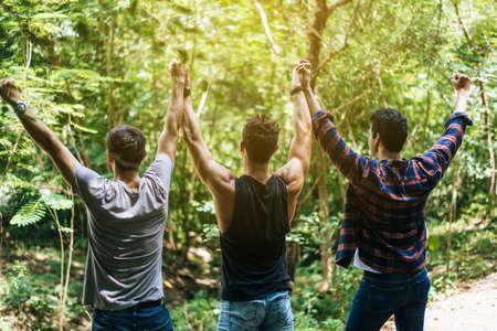 Happy men traveler friends hands raise up together at nature,Enjoying backpacking concept,Back view Foto de archivo - 133744032