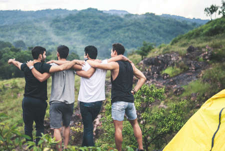 Cheerful young  man traveler friends hugging with hands raise up together at nature,Enjoying backpacking concept,Back view Foto de archivo - 133744057