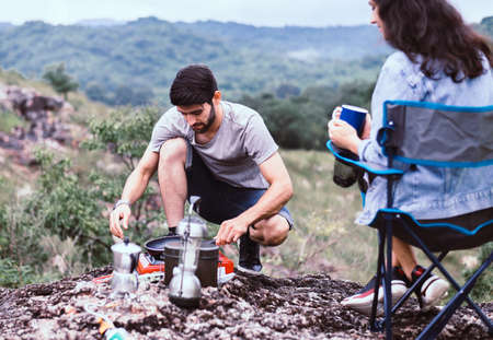 Couple lover cooking food for breakfast outside tent together,Enjoying camping concept Foto de archivo - 133744064