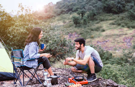 Couple lover cooking food for breakfast outside tent together,Enjoying camping concept Foto de archivo - 133744065