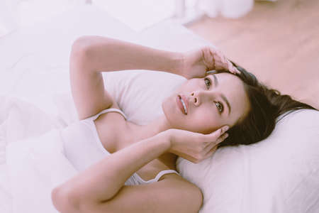 Portrait of young pretty asian woman lying down on bedroom,Sexy female and perfect skin,Close up face