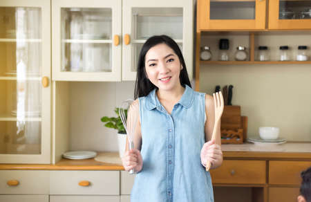 Beautiful young asian woman cooking in the kitchen,Happy and smiling