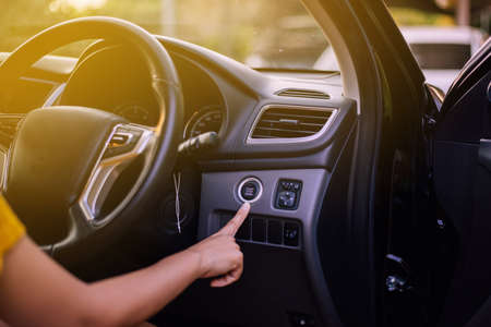 Hand woman driver push on car engine power system technology button,Finger pressing on start stop engine Фото со стока