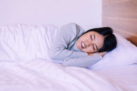 Beautiful asian woman sleeping on bed and grinding teeth,Female tiredness and stress Standard-Bild