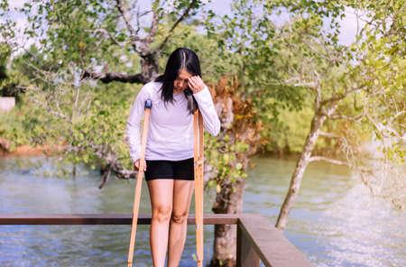 Patiente asiatique utilisant une béquille et une jambe cassée pour marcher dans la nature Banque d'images