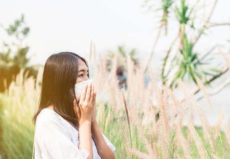 Junge asiatische Frau mit Maske und Niesen wegen Allergie mit Feld in der Natur